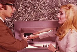 Photo shows man and woman using a cashpoint