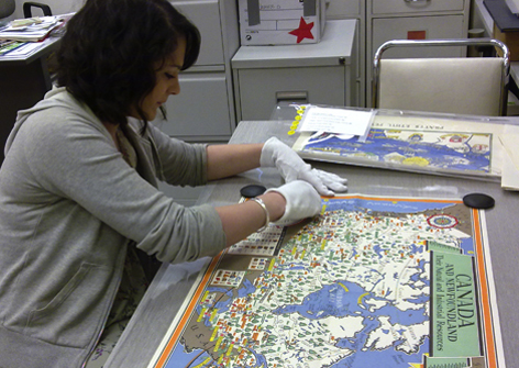 A UConn member works and studies a map of Canada.