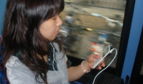 A Student using an iPod on the Bus