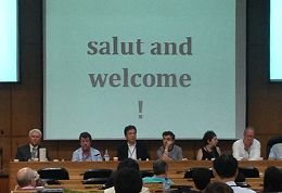 Conference photograph with 'Welcome and Salut' message on projector